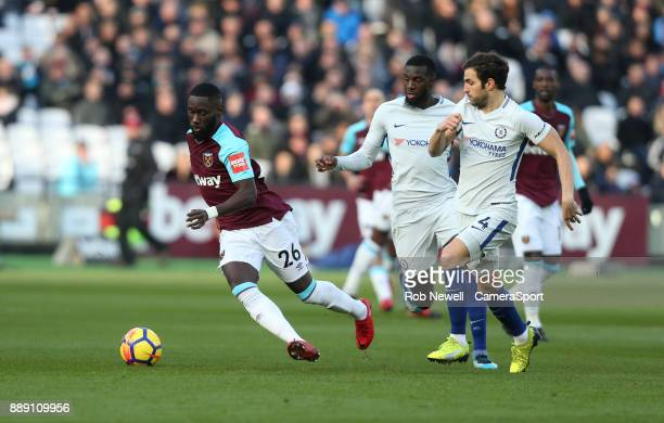 West Ham United's Arthur Masuaku dribbles away from Chelsea's Cesc Fabregas and Tiemoue Bakayoko during the Premier League match between West Ham...