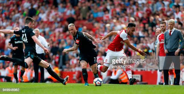 West Ham United's Austrian midfielder Marko Arnautovic fouls Arsenal's Gabonese striker PierreEmerick Aubameyang under the eye of Arsenal's French...