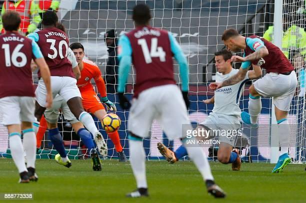 West Ham United's Austrian midfielder Marko Arnautovic shoots past Chelsea's Belgian goalkeeper Thibaut Courtois to score the opening goal of the...