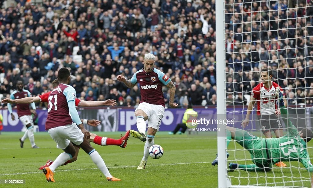 TOPSHOT - West Ham United's Austrian midfielder Marko Arnautovic (C) shoots to score their second goal past Southampton's English goalkeeper Alex McCarthy (R) during the English Premier League football match between West Ham United and Southampton at The London Stadium, in east London on March 31, 2018. / AFP PHOTO / Ian KINGTON / RESTRICTED TO EDITORIAL USE. No use with unauthorized audio, video, data, fixture lists, club/league logos or 'live' services. Online in-match use limited to 75 images, no video emulation. No use in betting, games or single club/league/player publications. /