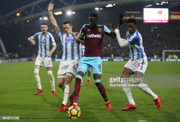 West Ham United's Cheikhou Kouyate gets in between Huddersfield Town's Jonathan Hogg and Terence Kongolo during the Premier League match between...