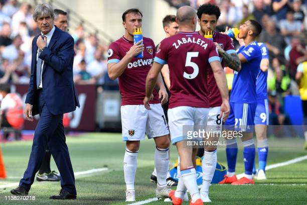 West Ham United's Chilean manager Manuel Pellegrini looks on as West Ham United's players take a drink during the English Premier League football...