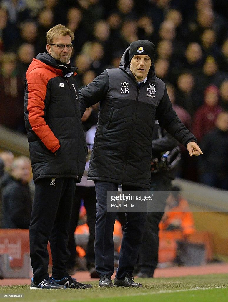 West Ham United's Croatian manager Slaven Bilic (R) and Liverpool's German manager Jurgen Klopp look on during the English FA Cup fourth round football match between Liverpool and West Ham United at Anfield in Liverpool, north west England, on January 30, 2016. / AFP / PAUL ELLIS / RESTRICTED TO EDITORIAL USE. No use with unauthorized audio, video, data, fixture lists, club/league logos or 'live' services. Online in-match use limited to 75 images, no video emulation. No use in betting, games or single club/league/player publications. /