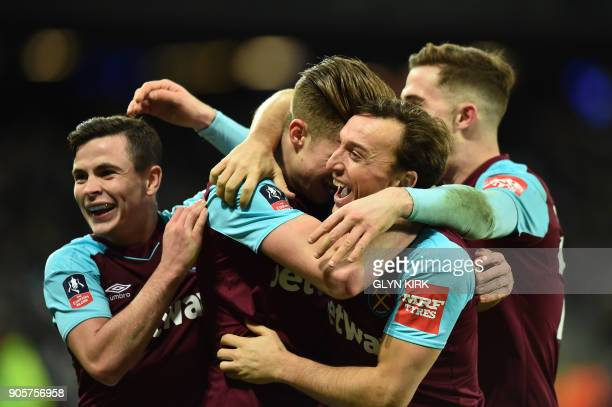 West Ham United's English defender Reece Burke celebrates scoring the team's first goal with teammates during the FA Cup third round replay football...