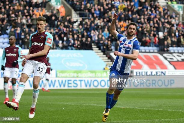 West Ham United's English defender Reece Burke reacts as Wigan Athletic's Englishborn Northern Irish striker Will Grigg celebrates scoring the...