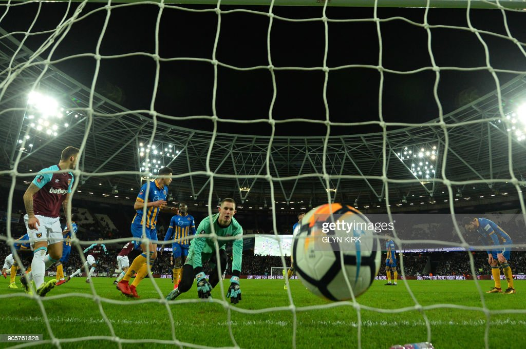 West Ham United's English defender Reece Burke scores past Shrewsbury Town's English goalkeeper Dean Henderson during the FA Cup third round replay football match between West Ham United and Shrewsbury Town at The London Stadium, in east London on January 16, 2018. / AFP PHOTO / Glyn KIRK / RESTRICTED TO EDITORIAL USE. No use with unauthorized audio, video, data, fixture lists, club/league logos or 'live' services. Online in-match use limited to 75 images, no video emulation. No use in betting, games or single club/league/player publications. /