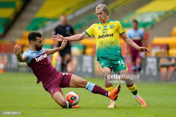 West Ham United's English defender Ryan Fredericks fights for the ball with Norwich City's English midfielder Todd Cantwell during the English...