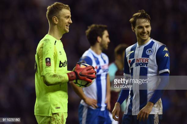 West Ham United's English goalkeeper Joe Hart and Wigan Athletic's English midfielder Nick Powell share a joke during the English FA Cup fourth round...