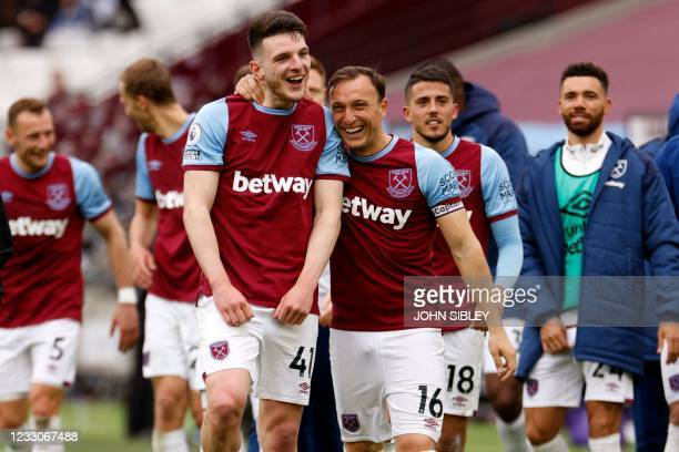 West Ham United's English midfielder Declan Rice and West Ham United's English midfielder Mark Noble share a joke as they celebrate on the pitch...