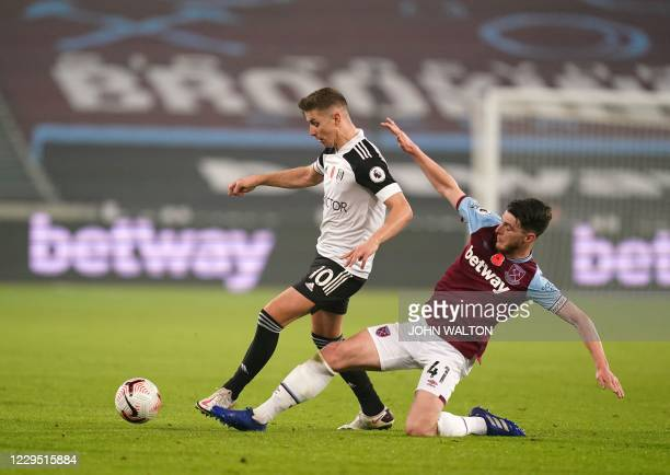 West Ham United's English midfielder Declan Rice slides in to tackle Fulham's English midfielder Tom Cairney during the English Premier League...