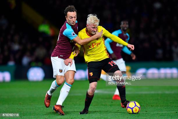 West Ham United's English midfielder Mark Noble challenges Watford's English midfielder Will Hughes during the English Premier League football match...