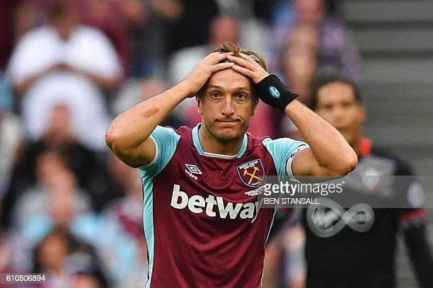 West Ham United's English midfielder Mark Noble reacts after commiting a foul that earned him a yellow card during the English Premier League...