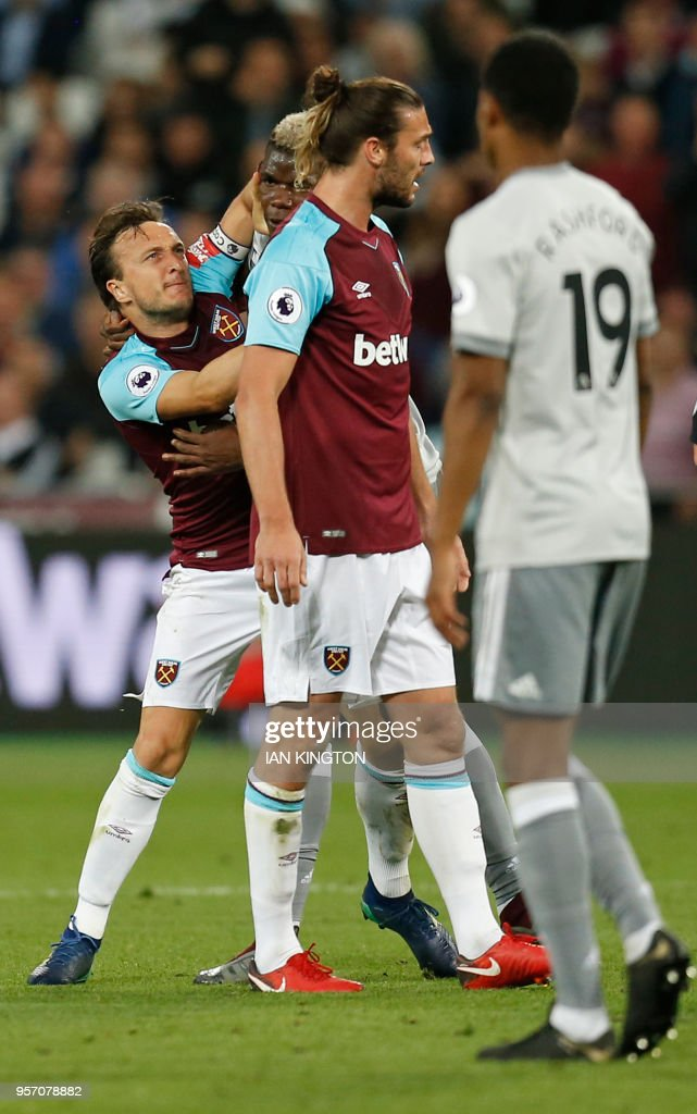 West Ham United's English midfielder Mark Noble (L) remonstrates with Manchester United's French midfielder Paul Pogba (2L) during the English Premier League football match between West Ham United and Manchester United at The London Stadium, in east London on May 10, 2018. (Photo by Ian KINGTON / AFP) / RESTRICTED TO EDITORIAL USE. No use with unauthorized audio, video, data, fixture lists, club/league logos or 'live' services. Online in-match use limited to 75 images, no video emulation. No use in betting, games or single club/league/player publications. /