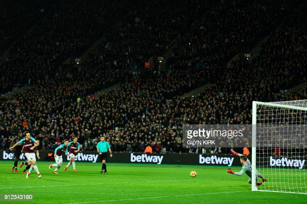 West Ham United's English midfielder Mark Noble scores from the penalty spot his team's first goal to equalise 11 during the English Premier League...