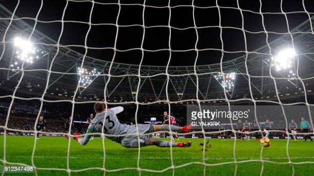 West Ham United's English midfielder Mark Noble slots his penalty past Crystal Palace's Welsh goalkeeper Wayne Hennessey to score their first goal to...