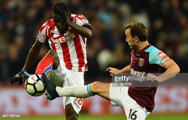 West Ham United's English midfielder Mark Noble vies with Stoke City's Senegalese striker Mame Biram Diouf during the English Premier League football...