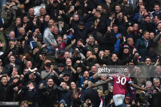 West Ham United's English midfielder Michail Antonio celebrates in front of the West Ham fans after scoring the opening goal of the English Premier...