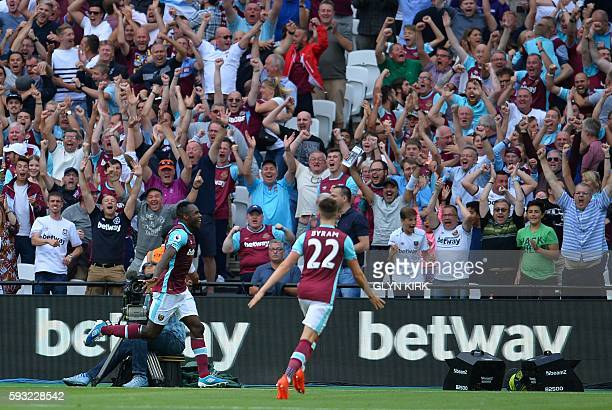 West Ham United's English midfielder Michail Antonio celebrates in front of the home supporters after scoring the opening goal of the English Premier...