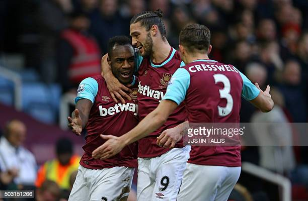 West Ham United's English midfielder Michail Antonio celebrates with West Ham United's English striker Andy Carroll and West Ham United's English...