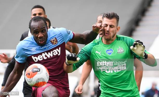 West Ham United's English midfielder Michail Antonio fights for the ball with Newcastle United's Slovakian goalkeeper Martin Dubravka during the...