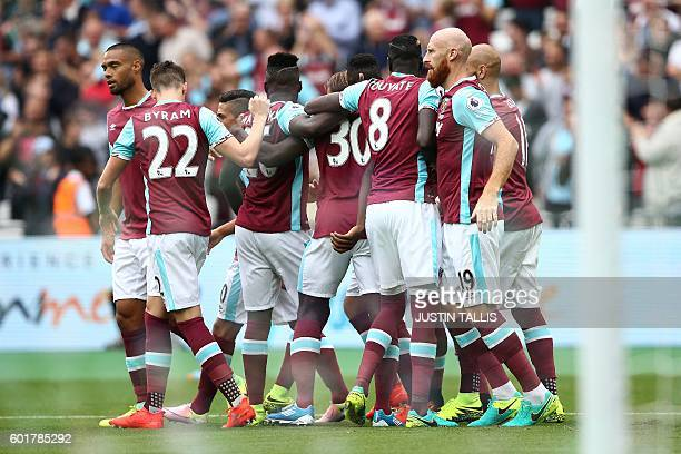 West Ham United's English midfielder Michail Antonio is mobbed by teammates as he celebrates scoring his team's first goal during the English Premier...