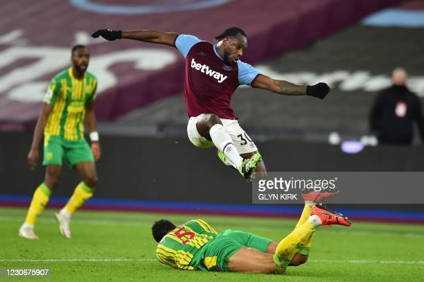 West Ham United's English midfielder Michail Antonio leaps over West Bromwich Albion's English defender Kyle Bartley during the English Premier...