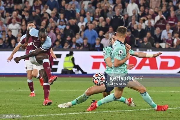 West Ham United's English midfielder Michail Antonio shoots through players to score their third goal during the English Premier League football...