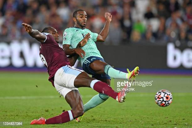 West Ham United's English midfielder Michail Antonio shoots to score their fourth goal under pressure from Leicester City's Portuguese defender...
