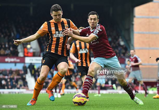 West Ham United's English midfielder Stewart Downing vies with Hull City's Northern Irish defender Alex Bruce during the English Premier League...