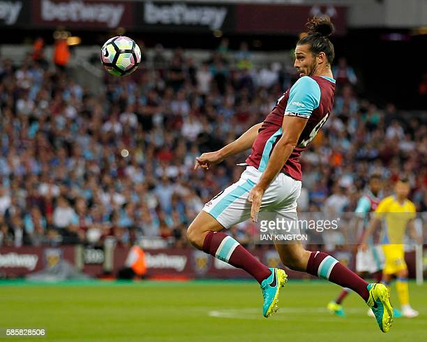 West Ham United's English striker Andy Carroll heads the ball in the buildup to the second goal during the qualifying third round second leg Europa...