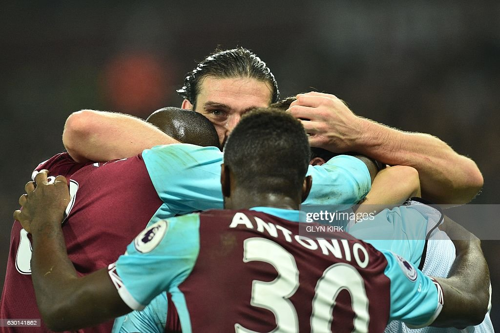 West Ham United's English striker Andy Carroll (C) joins teammates in celebrating with West Ham United's English midfielder Mark Noble after he scores the opening goal from the penalty spot during the English Premier League football match between West Ham United and Hull City at The London Stadium, in east London on December 17, 2016. / AFP / Glyn KIRK / RESTRICTED TO EDITORIAL USE. No use with unauthorized audio, video, data, fixture lists, club/league logos or 'live' services. Online in-match use limited to 75 images, no video emulation. No use in betting, games or single club/league/player publications. /