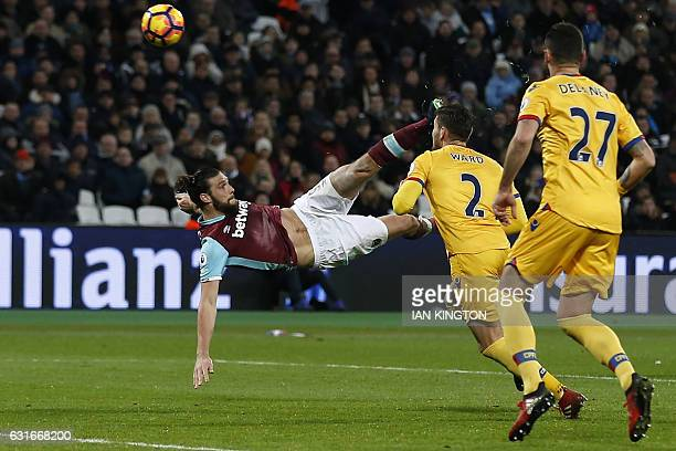 West Ham United's English striker Andy Carroll shoots to score their second goal with this bicycle kick during the English Premier League football...