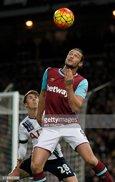 West Ham United's English striker Andy Carroll vies with Tottenham Hotspur's English midfielder Tom Carroll during the English Premier League...