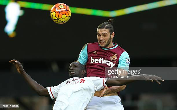 West Ham United's English striker Andy Carroll wins a header from Liverpool's French defender Mamadou Sakho during the English Premier League...