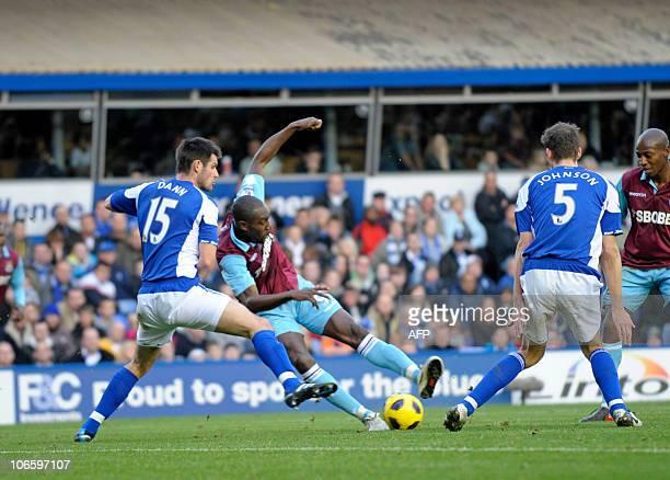 West Ham United's English striker Carlton Cole shoots past Birmingham City's English defenders, Scott Dann and Roger Johnson during the English...