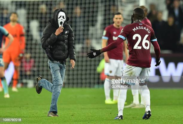 West Ham United's French defender Arthur Masuaku interacts with a pitch invader during the English League Cup football match between West Ham United...