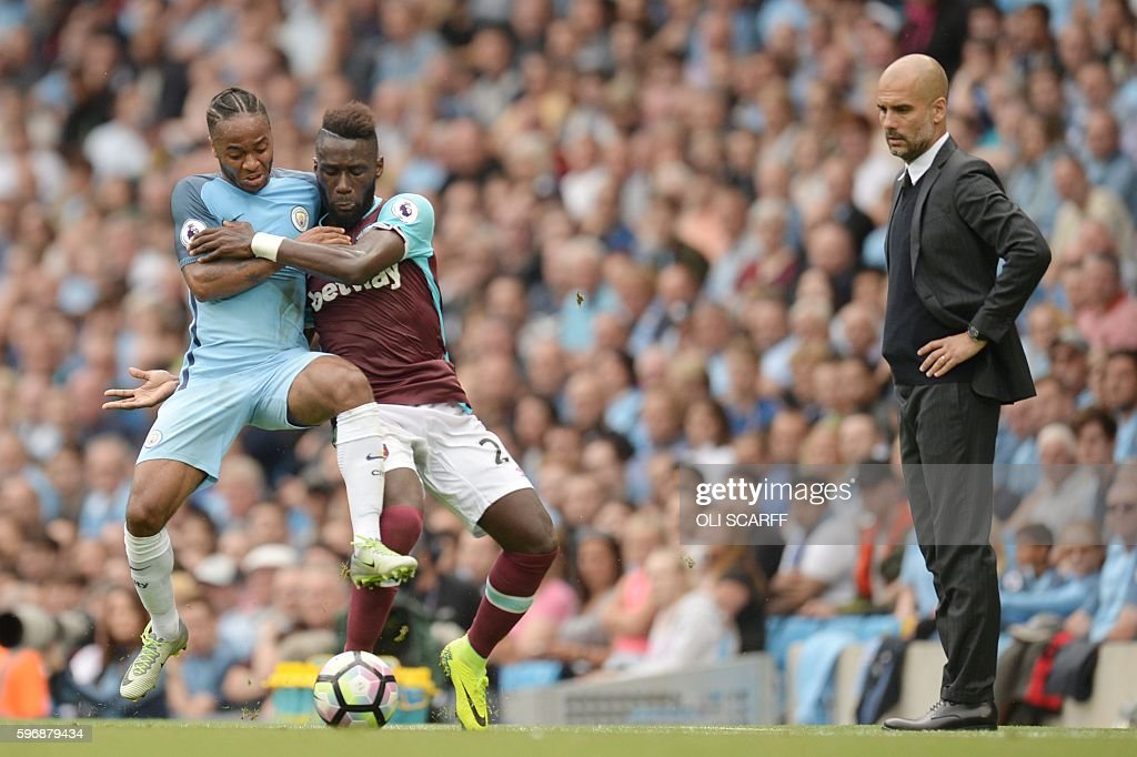 TOPSHOT - West Ham United's French defender Arthur Masuaku vies with Manchester City's English midfielder Raheem Sterling (L) as Manchester City's Spanish manager Pep Guardiola (R) looks on during the English Premier League football match between Manchester City and West Ham United at the Etihad Stadium in Manchester, north west England, on August 28, 2016. / AFP / OLI SCARFF / RESTRICTED TO EDITORIAL USE. No use with unauthorized audio, video, data, fixture lists, club/league logos or 'live' services. Online in-match use limited to 75 images, no video emulation. No use in betting, games or single club/league/player publications. /