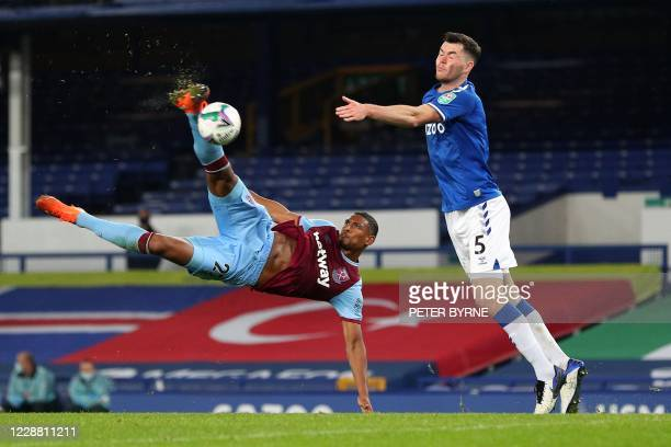 West Ham United's French striker Sebastien Haller goes airborne to take a shot at goal past Everton's English defender Michael Keane during the...