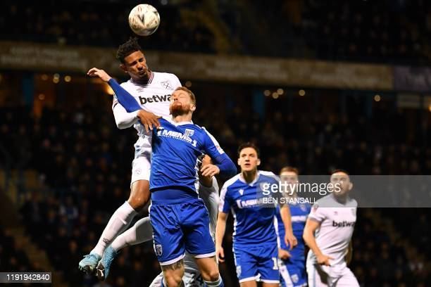 West Ham United's French striker Sebastien Haller jumps to win a header under pressure from Gillingham's English defender Connor Ogilvie during the...