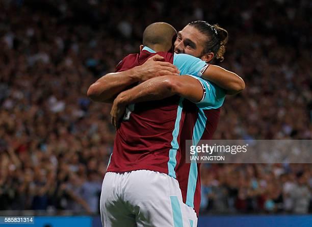 West Ham United's Frenchborn Algerian midfielder Sofiane Feghouli celebrates with West Ham United's English striker Andy Carroll after scoring their...