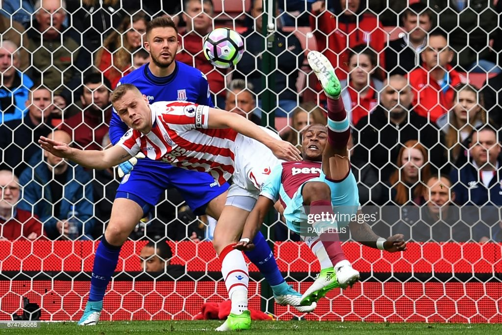 TOPSHOT - West Ham United's French-born Ghanaian midfielder Andre Ayew (R) tries an overhaed a shot, which is saved by Stoke City's English goalkeeper Jack Butland during the English Premier League football match between Stoke City and West Ham United at the Bet365 Stadium in Stoke-on-Trent, central England on April 29, 2017. / AFP PHOTO / Paul ELLIS / RESTRICTED TO EDITORIAL USE. No use with unauthorized audio, video, data, fixture lists, club/league logos or 'live' services. Online in-match use limited to 75 images, no video emulation. No use in betting, games or single club/league/player publications. /