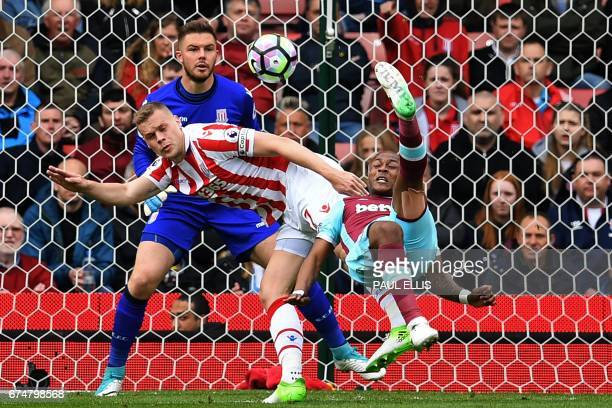 TOPSHOT West Ham United's Frenchborn Ghanaian midfielder Andre Ayew tries an overhaed a shot which is saved by Stoke City's English goalkeeper Jack...
