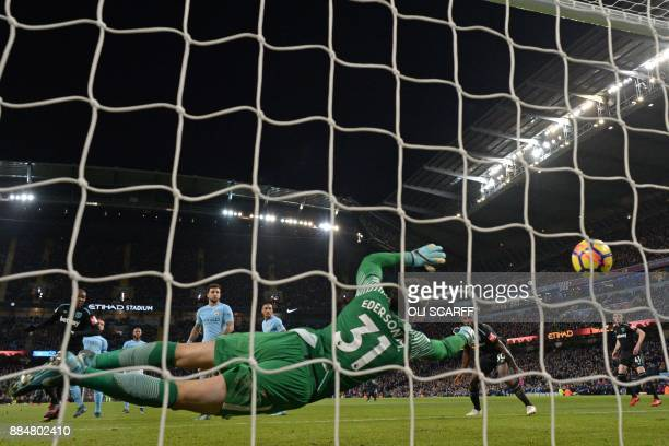 West Ham United's Italian defender Angelo Ogbonna watches the ball pass Manchester City's Brazilian goalkeeper Ederson as he scores the opening goal...