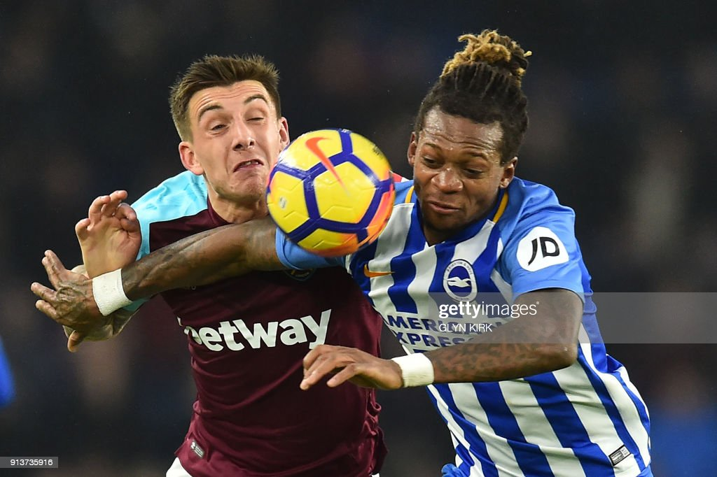 TOPSHOT - West Ham United's Jordan Hugil (L) vies with Brighton's Cameroonian defender Gaetan Bong during the English Premier League football match between Brighton and Hove Albion and West Ham United at the American Express Community Stadium in Brighton, southern England on February 3, 2018. / AFP PHOTO / Glyn KIRK / RESTRICTED TO EDITORIAL USE. No use with unauthorized audio, video, data, fixture lists, club/league logos or 'live' services. Online in-match use limited to 75 images, no video emulation. No use in betting, games or single club/league/player publications. /