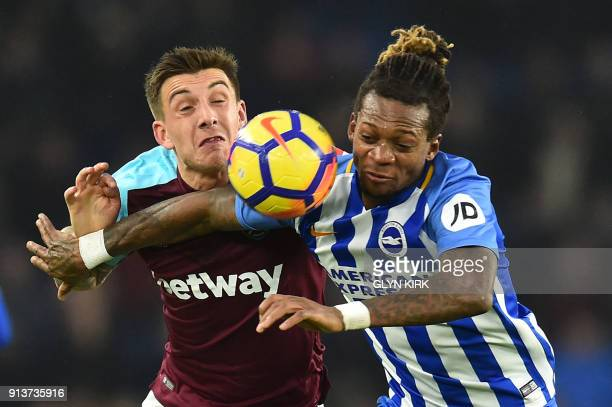 TOPSHOT West Ham United's Jordan Hugil vies with Brighton's Cameroonian defender Gaetan Bong during the English Premier League football match between...