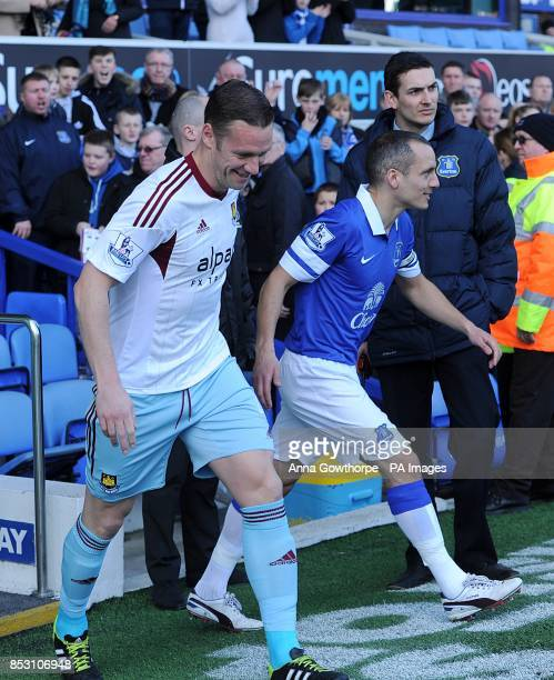 West Ham United's Kevin Nolan and Everton's Leon Osman walk out onto the pitch before kickoff