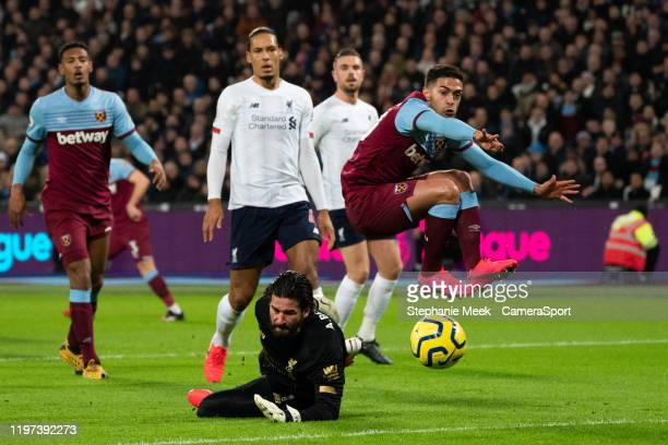 West Ham United's Manuel Lanzini battles with Liverpool's Alisson Becker during the Premier League match between West Ham United and Liverpool FC at...