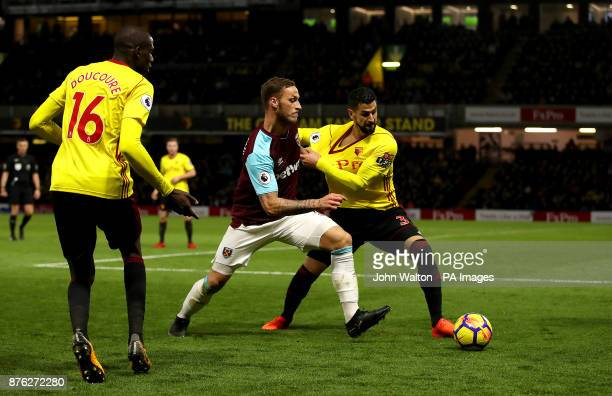 West Ham United's Marko Arnautovic and Watford's Miguel Britos battle for the ball during the Premier League match at Vicarage Road Watford