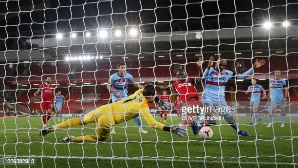 West Ham United's Polish goalkeeper Lukasz Fabianski dives to save a shot as West Ham United's Italian defender Angelo Ogbonna challenges Liverpool's...