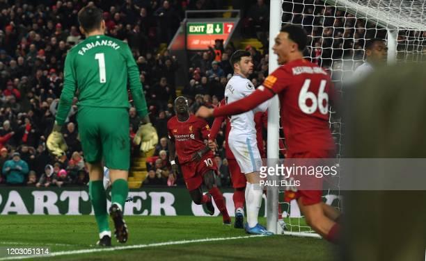 West Ham United's Polish goalkeeper Lukasz Fabianski reacts as Liverpool's English defender Trent Alexander-Arnold celebrates after Liverpool's...